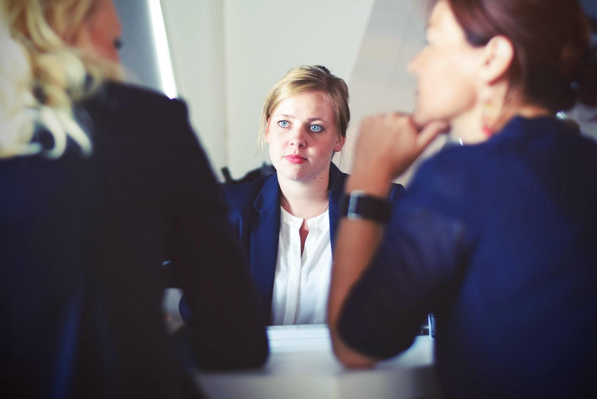 three business women sitting beside table