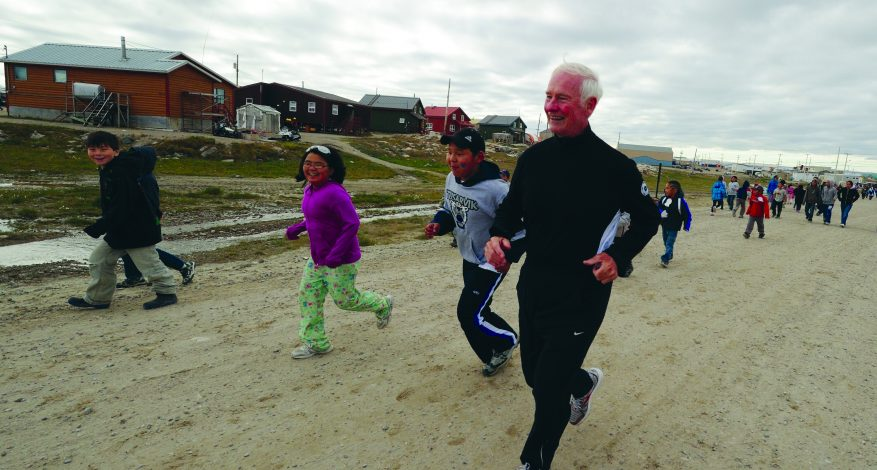 The Right Honourable David Johnston runs with children during an official visit to Repulse Bay, Nunavut, on Aug. 18, 2011. (Courtesy of the Rideau Hall Foundation)