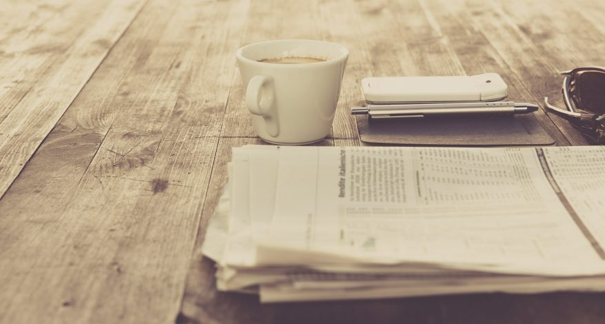 folded newspaper on wooden table beside coffee cup and cellphone