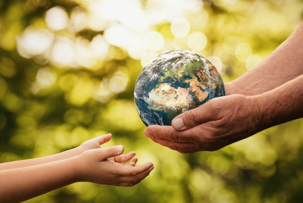 Close up of senior hands giving small planet earth to a child