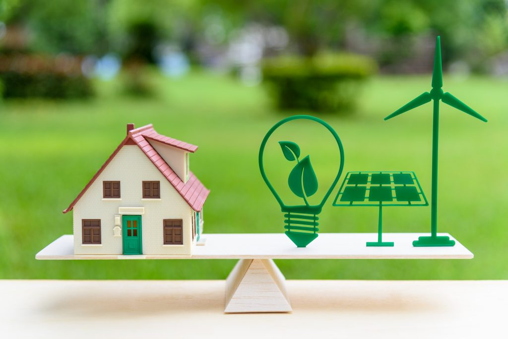 House model, light bulb with green leaf, solar panel, wind mill on wood balance scale, depicts the awareness of environment.