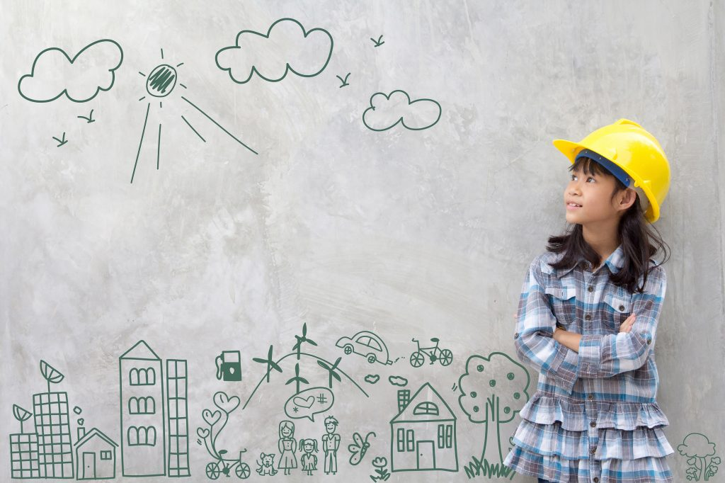 Little girl wearing construction hat against wall with cityscape drawn on it