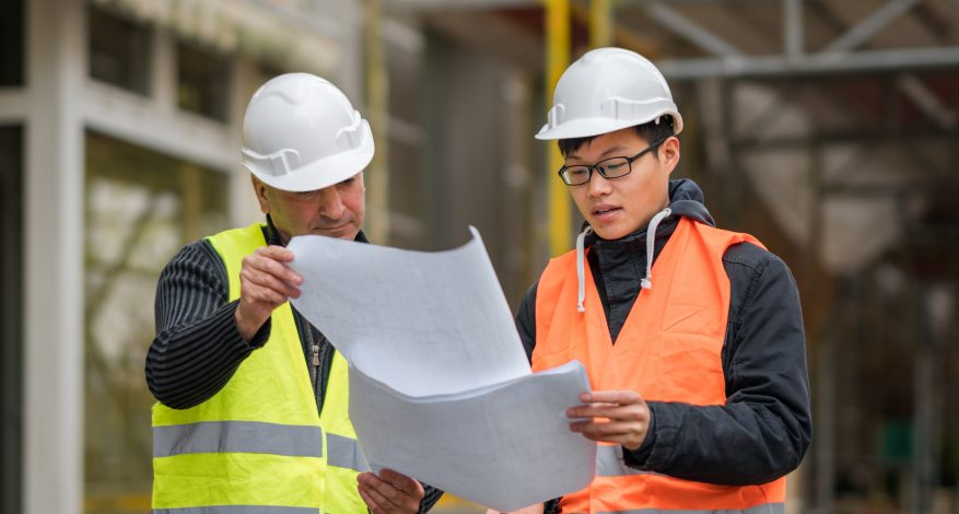 apprentice at work on construction site with senior engineer.