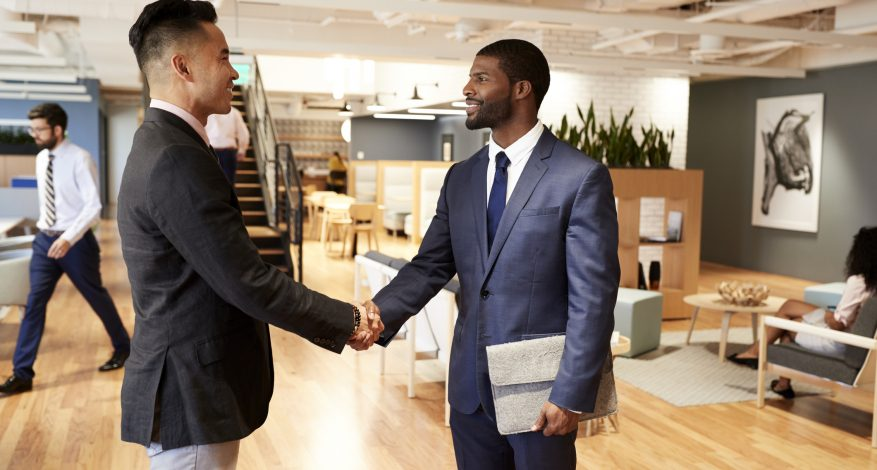 Two Businessmen Meeting And Shaking Hands In Modern Open Plan Office