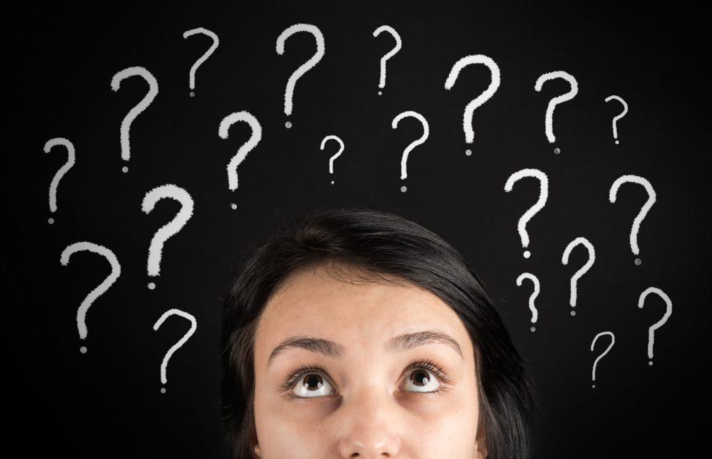 confused woman looking up at question marks above head