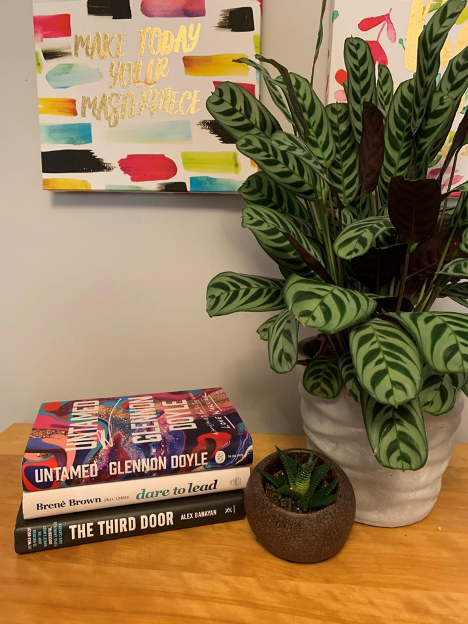 stack of books beside plant on wooden table