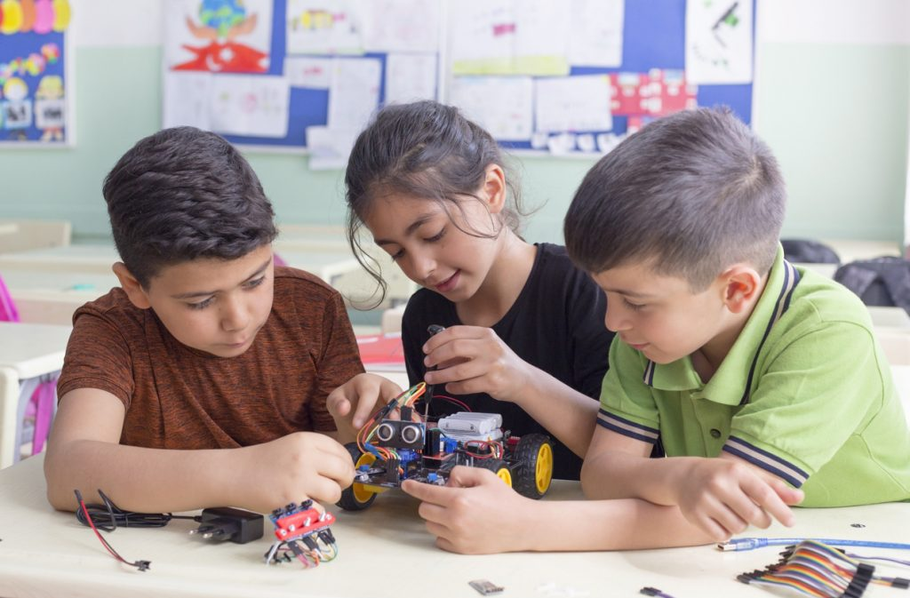 three students building robot in class