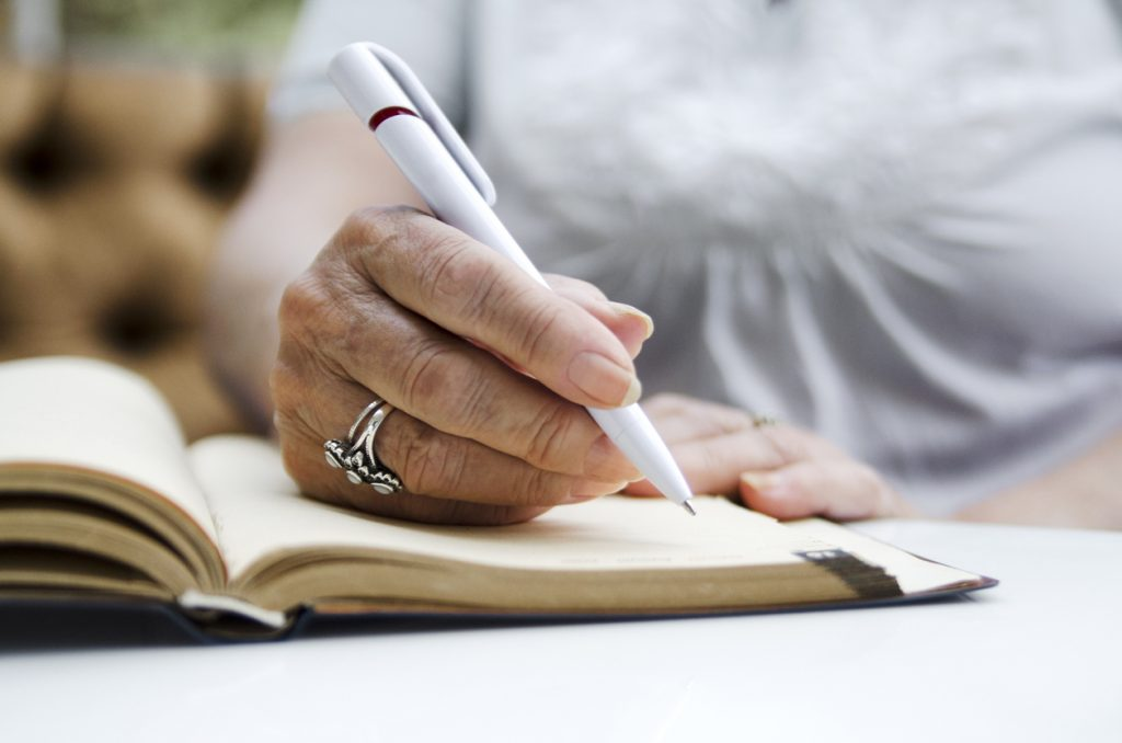 closeup of hands writing in notebook