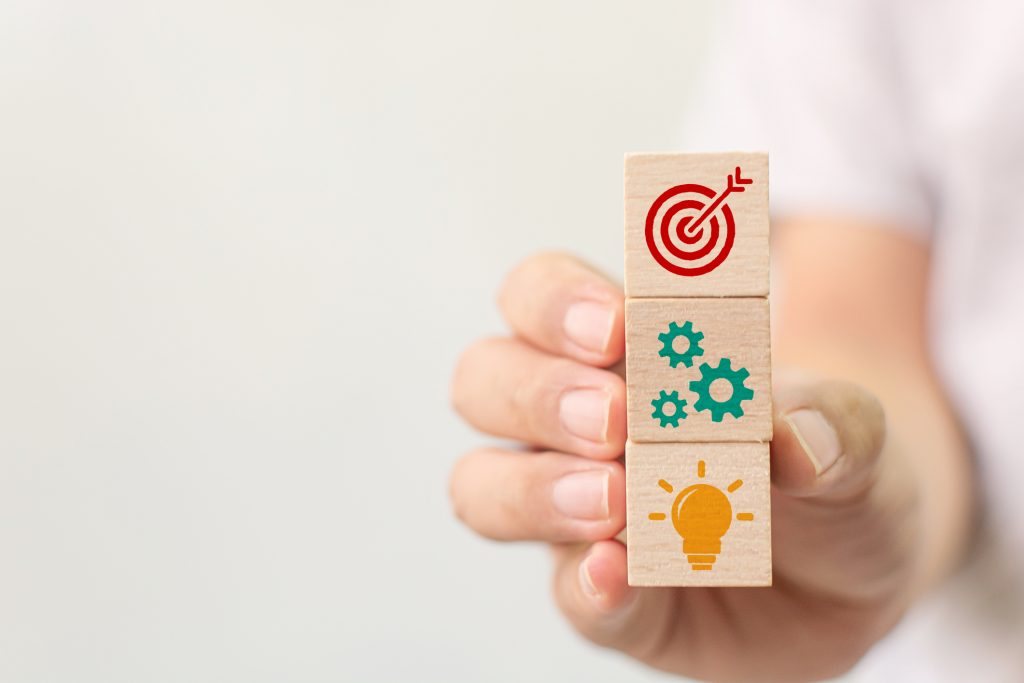 hand holding stack of wooden cubes with icons of target, gears and light bulb