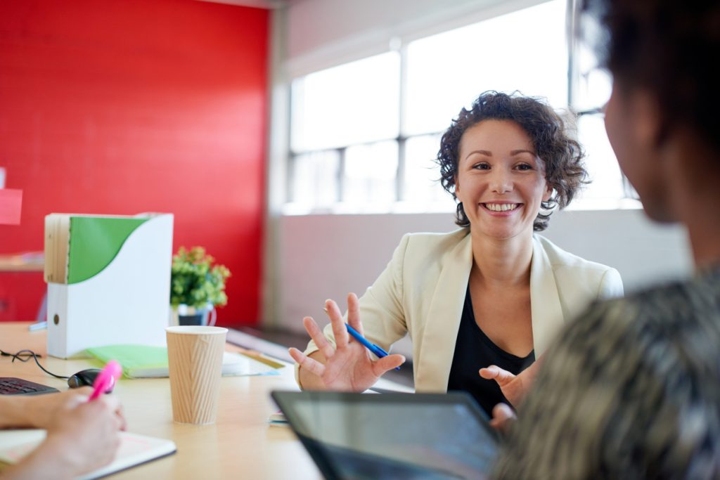 woman smiling and speaking to other people in office