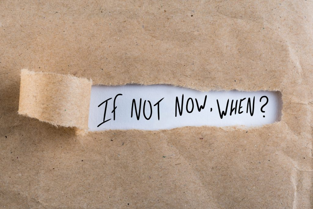 "torn brown paper revealing words underneath ""if not now, when?"""