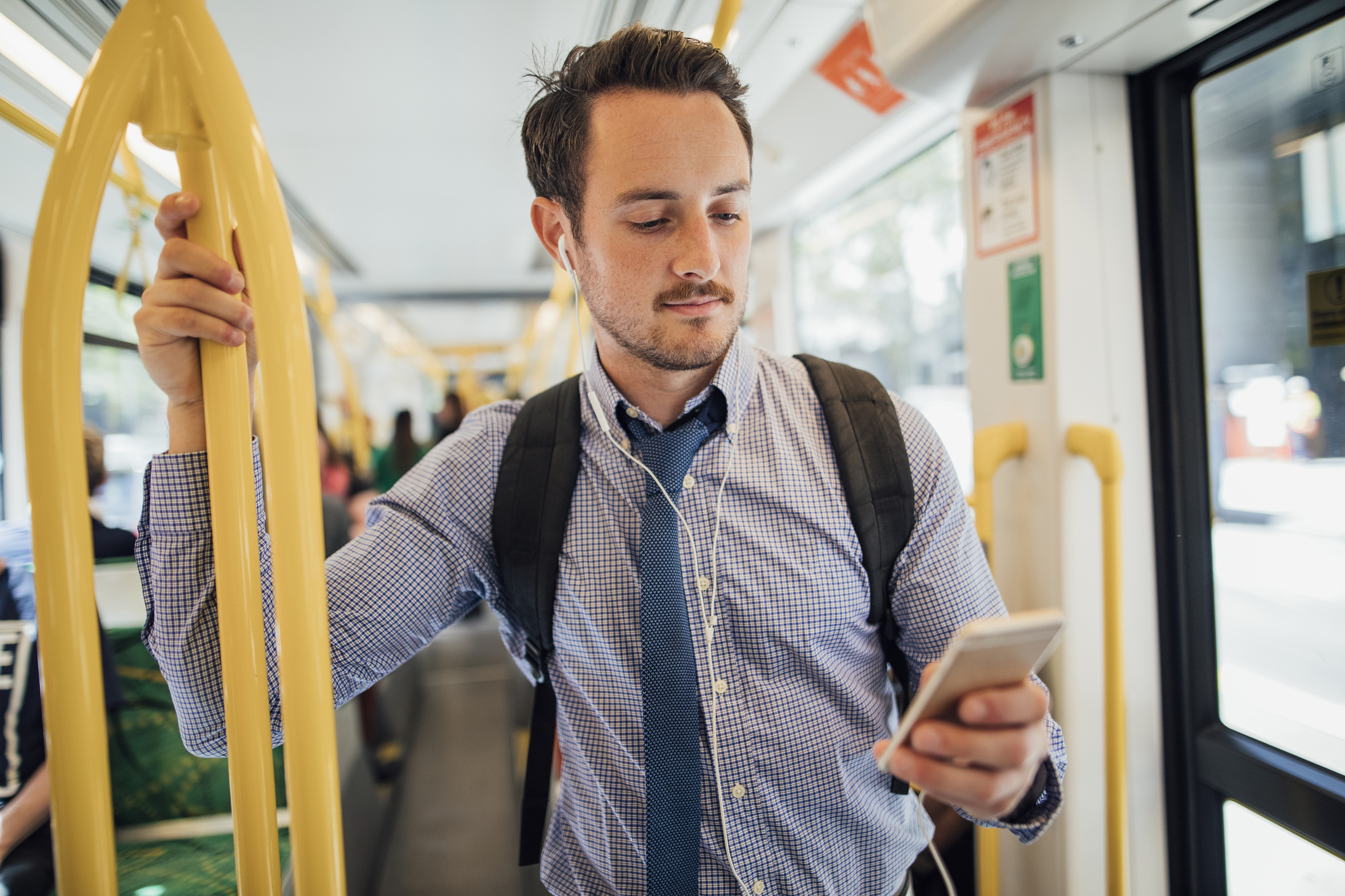 man wearing backpack on streetcar