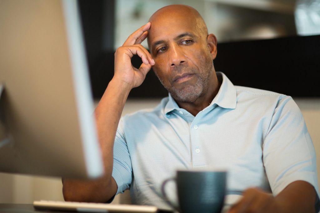 black man looking unhappy at desk at work