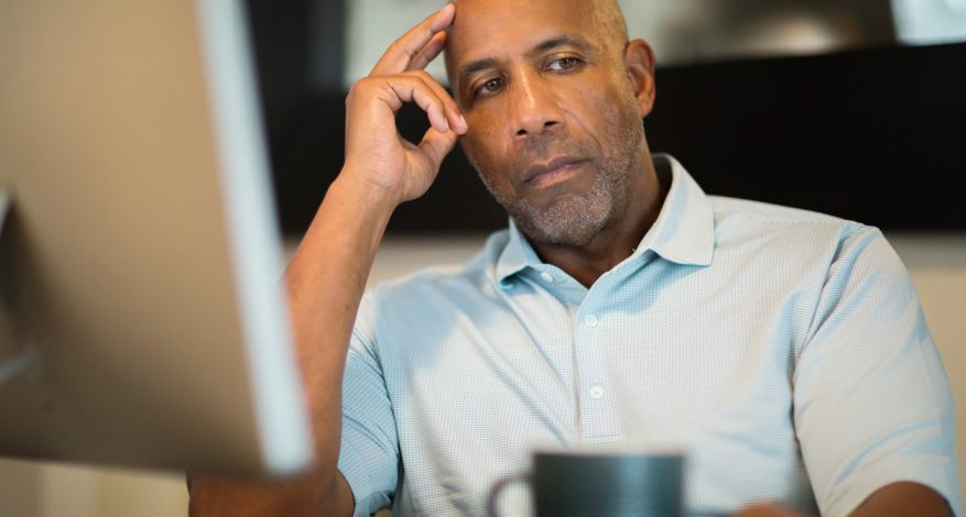 black man looking unhappy at desk at work