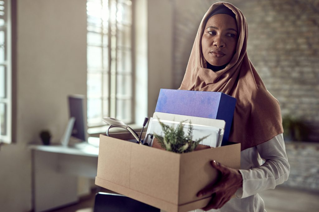 woman wearing hijab carries personal belongings out of office