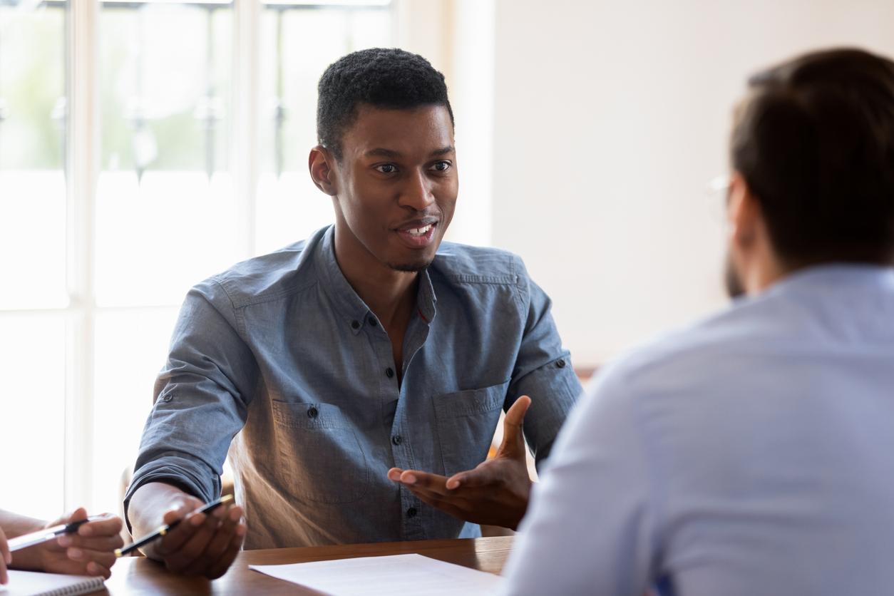 two men talking across table in office