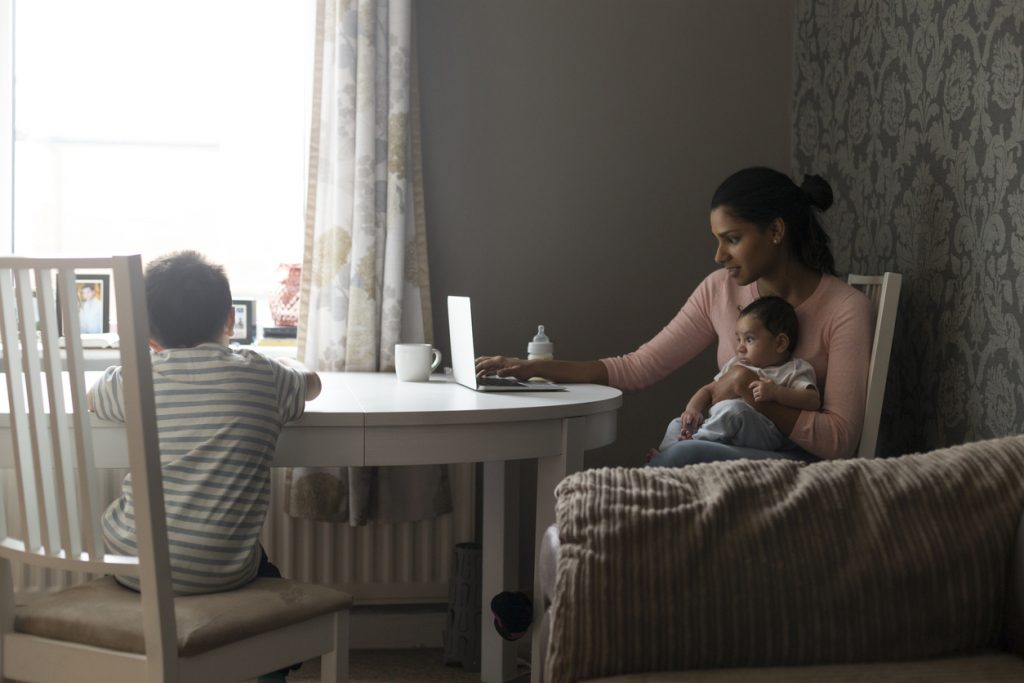 Young mother sitting at the table at home. She is holding her baby son whilst using a laptop. Her other son is sitting with his back to the camera, colouring in at the table.