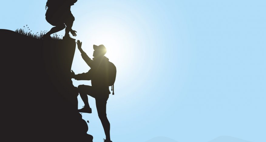 Silhouette of two people hiking climbing mountain and helping each other on blue sky