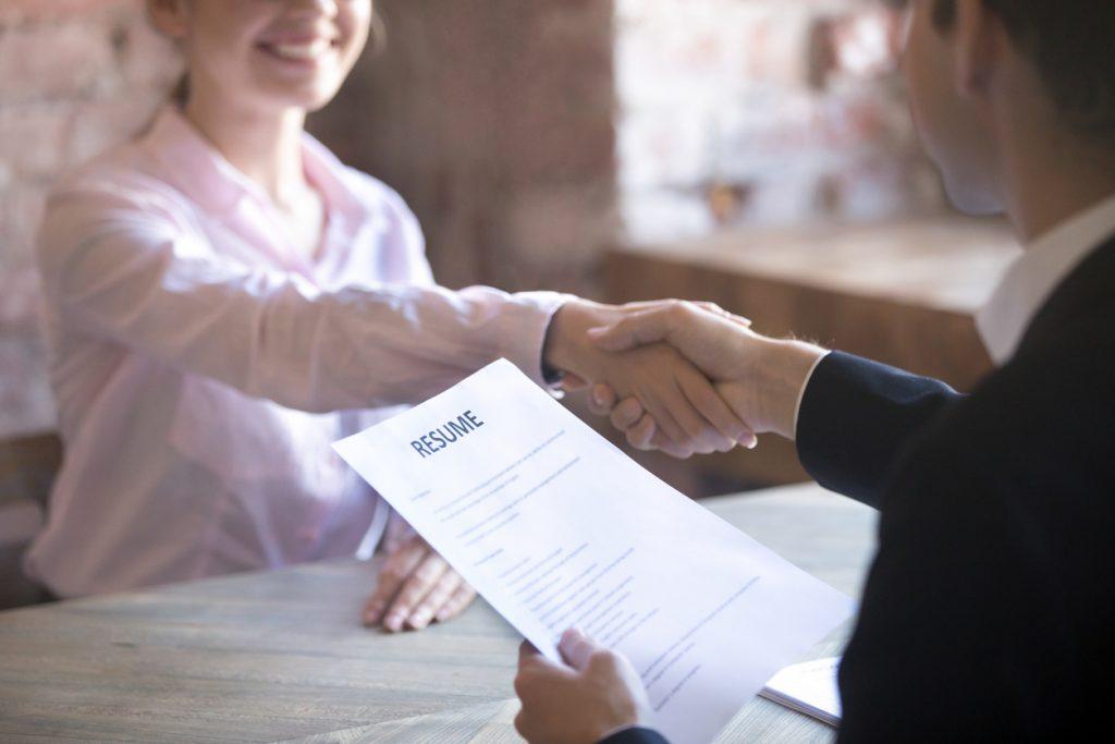 Smiling young woman and man handshake.