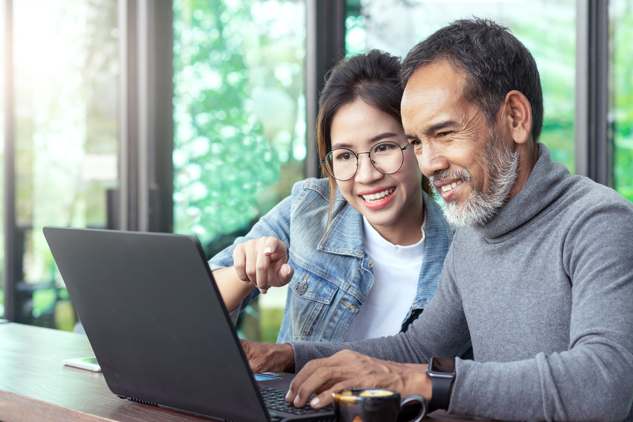 young woman helping older man using computer