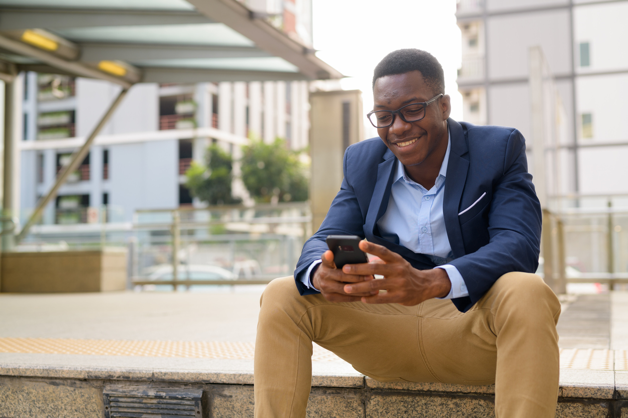 young man sitting outside train station looking at phone