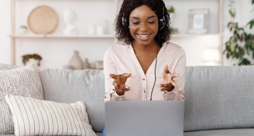 black woman having video call while sitting on couch