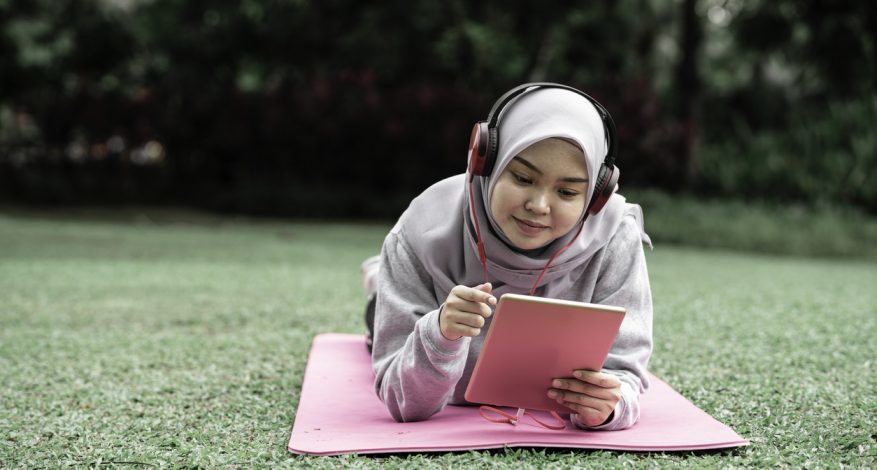 muslim teen girl using tablet in park