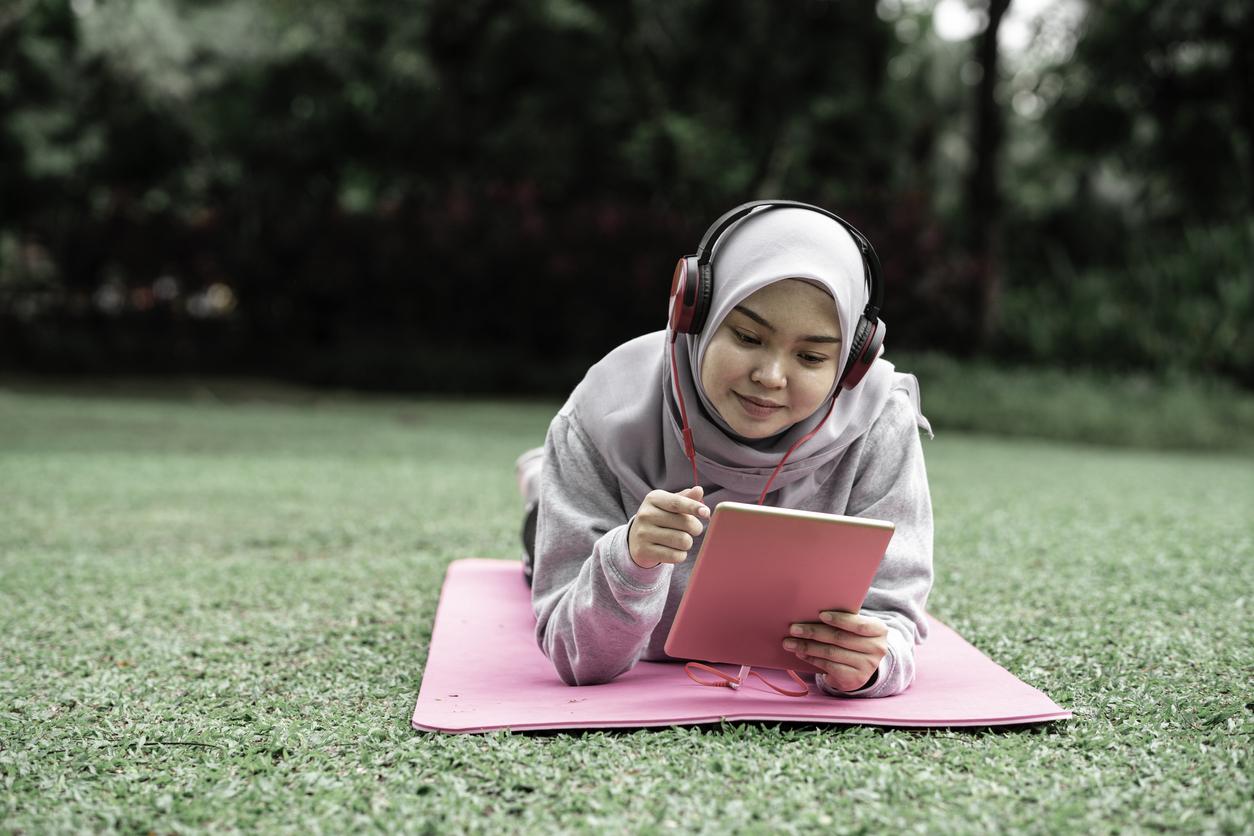 muslim teen girl using tablet in park