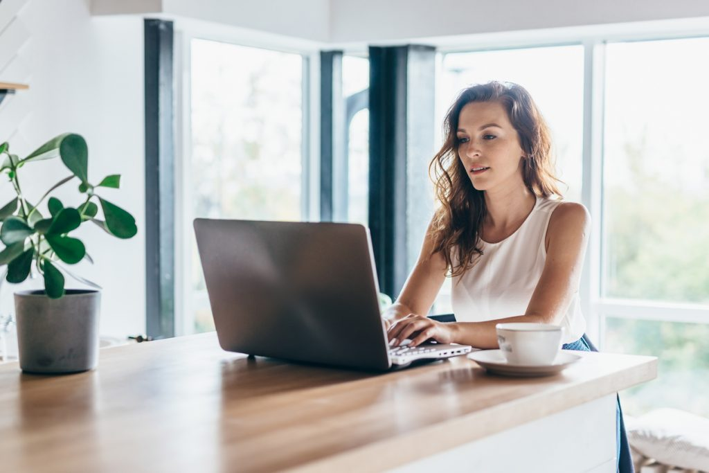 woman working on laptop on kitchen table