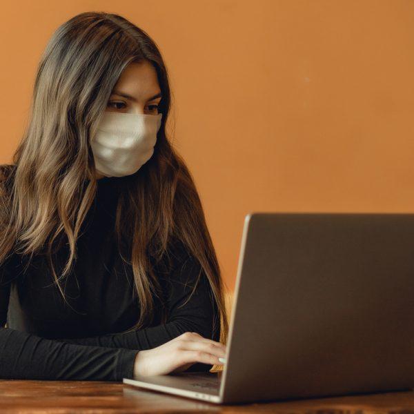 woman wearing face mask typing on laptop