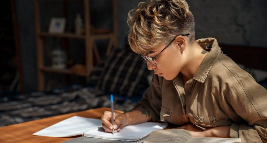 university student working on homework at desk
