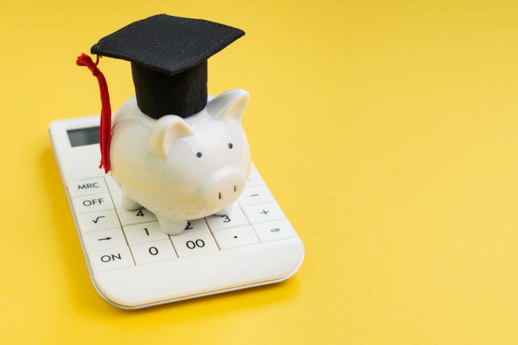 piggy bank wearing graduation cap sitting on top of calculator
