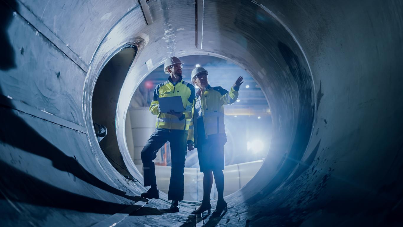 two engineers walking inside large pipe