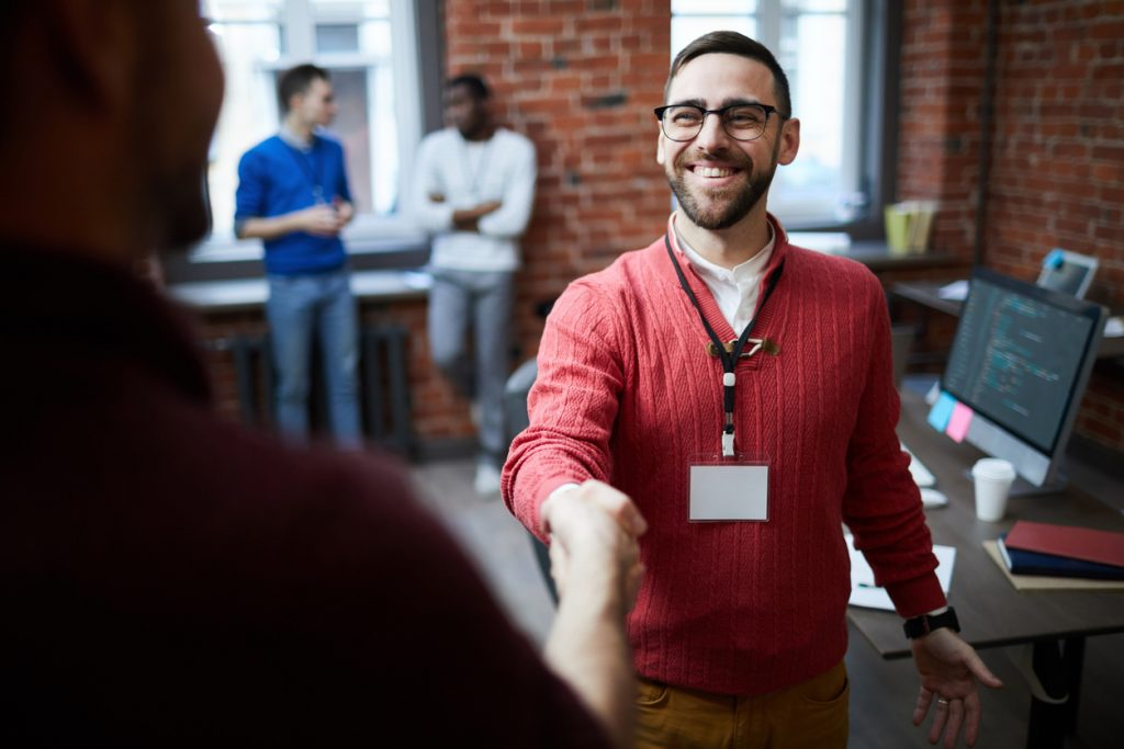 Man shaking hands with other person in office.