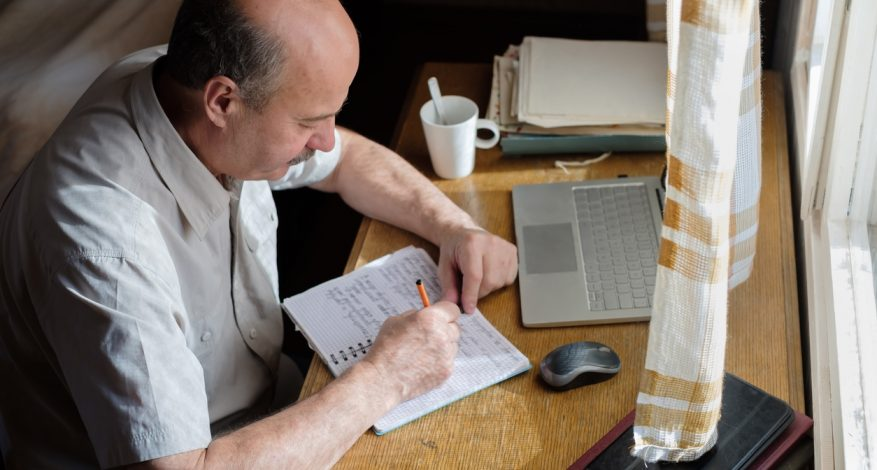 Older man sitting at desk and writing in notebook.