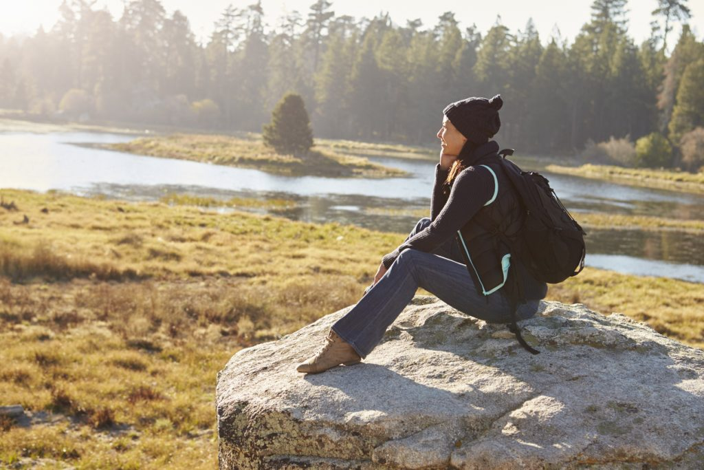 Young woman wearing backpack sitting on rock in forested area overlooking water.