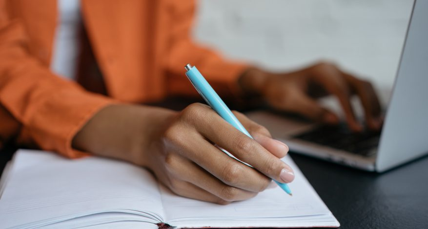 Close-up shot of hand holding pen and writing in noteboo