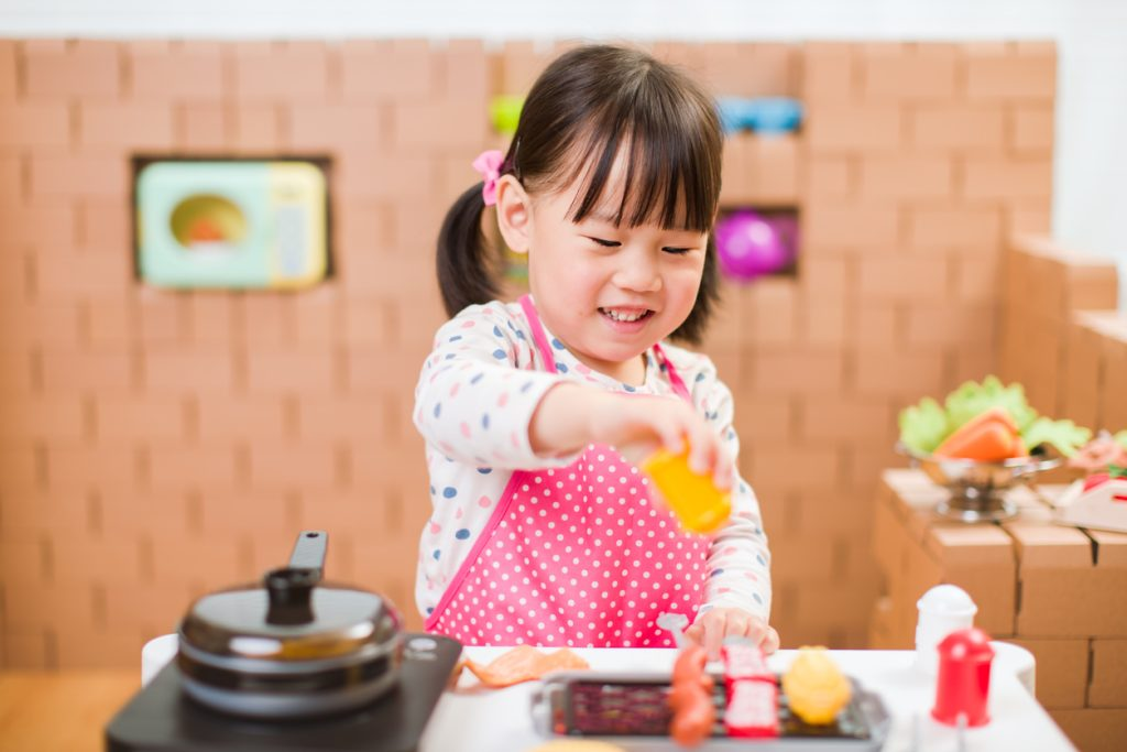 Little girl playing in toy kitchen.