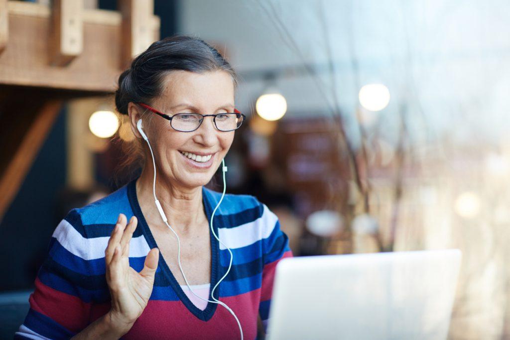 Woman wearing earphones and waving at computer screen.