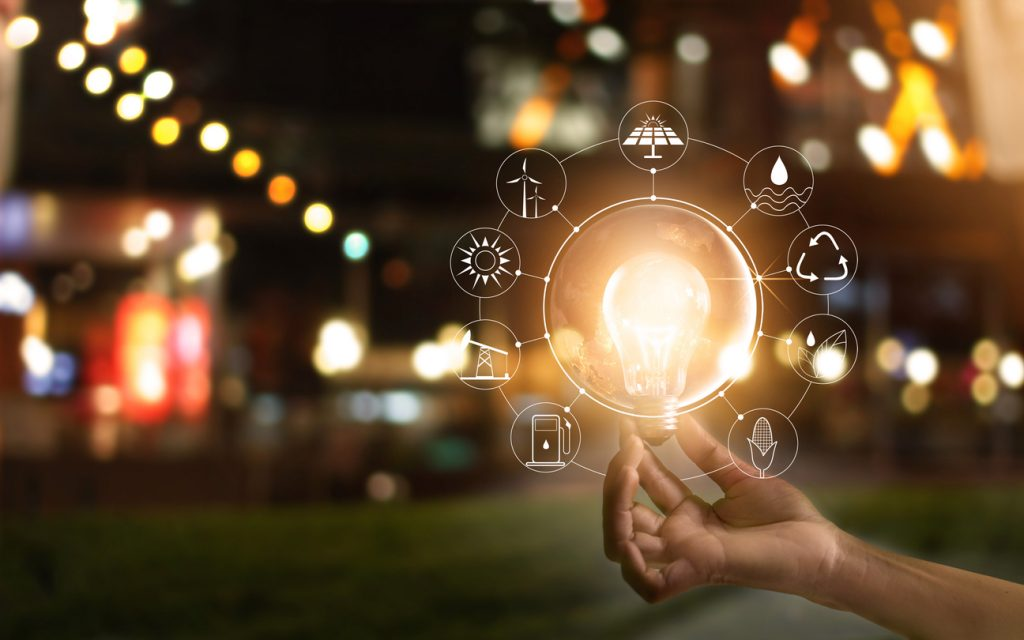 Hand holding light bulb with icons showing energy sources for renewable, sustainable development