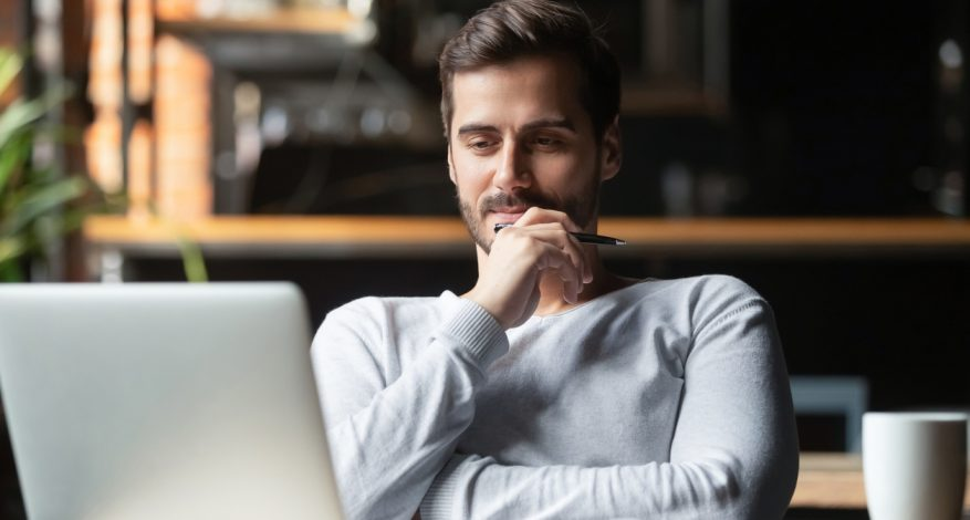 Man sitting at desk looking at laptop with pensive expression.