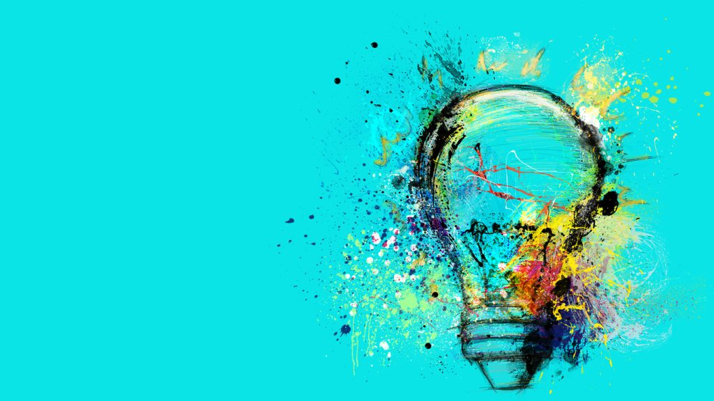 Lightbulb with paint splotches on bright blue background.